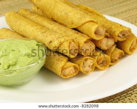 A plate of chicken taquitos with a side of guacamole. - stock photo