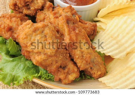 A plate of chicken wings closeup with potato chips