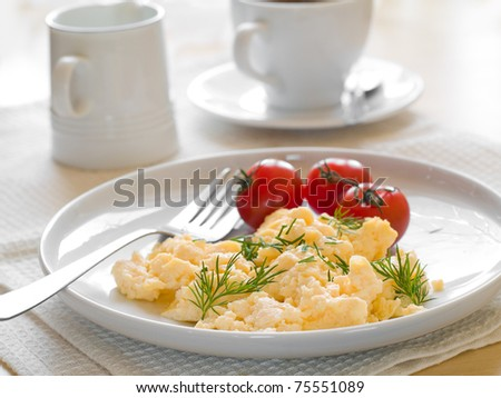 A plate of creamy scrambled eggs garnished with dill, a cup of coffee
