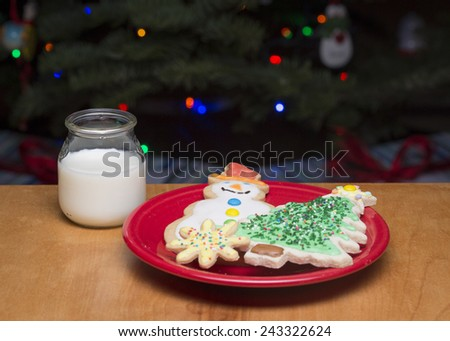 A plate of decorated sugar cookies and glass of milk for Santa. - stock photo