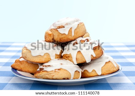 A plate of delicious cinnamon rolls coated with sugary frosting glaze. - stock photo