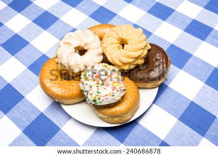 A plate of delicious, fresh donuts on a classic diner checkered blue and white tablecloth - stock photo