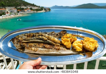 A plate of delicious grilled fish and a beautiful view of the blue sea