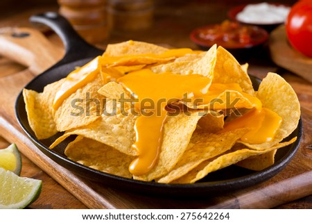 A plate of delicious plain nacho tortilla corn chips with cheese sauce. - stock photo