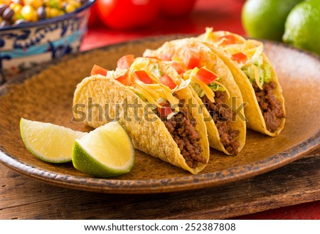 A plate of delicious tacos with lime, tomato, lettuce, and cheese. - stock photo