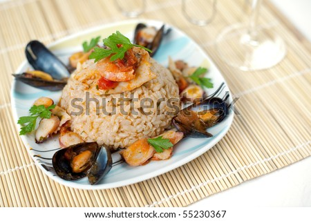 A plate of fancy italian risotto alla pescatora with seafood and fresh parsley - stock photo