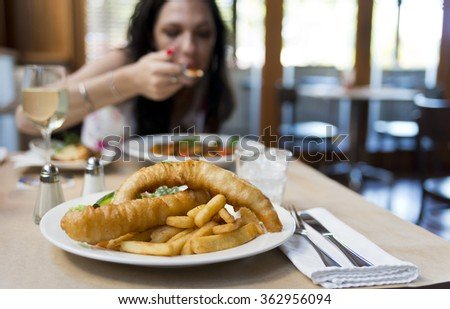A plate of fish and chips with salad focus on the fish and the chips. Shallow depth of field on fish and chips. Out of focus female at the other side of table eating. Brown paper table cloth.  - stock photo