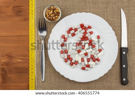 A plate of food supplements and cutlery. Diet food. Strict diet for athletes. - stock photo
