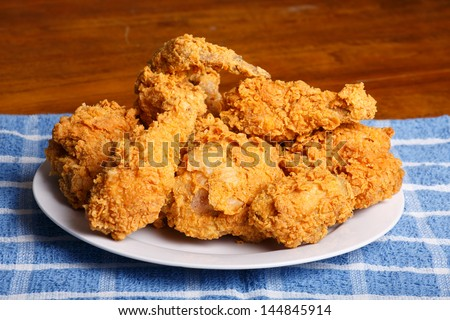 A plate of fresh, hot, crispy fried chicken on a blue plaid towel on a wood table - stock photo