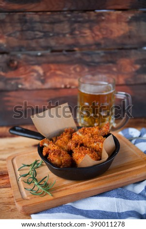 A plate of fresh, hot, crispy fried chicken with red sause on a blue plaid towel on a wood table. Snack to cold beer.  copy space - stock photo