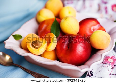 a plate of fresh peaches and apricots beautiful