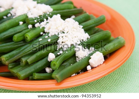 A plate of fresh, steamed, organic green beans, sprinkled with feta cheese. - stock photo