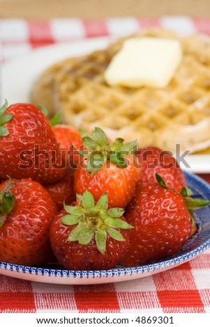 A plate of fresh strawberries. Waffles and butter in the background. Shallow dof. - stock photo