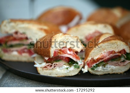 a plate of fresh Submarine Sandwiches by a nice swimming pool