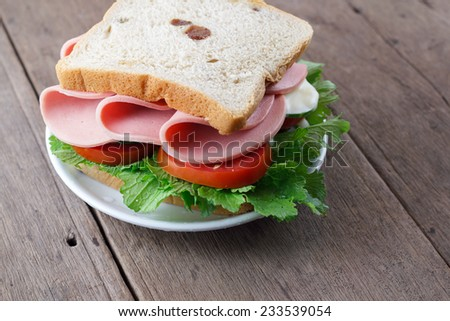 A plate of home made fresh ham tomato and lettuce sandwich on wooden table