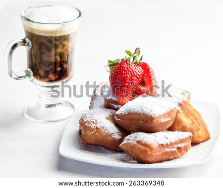 A plate of homemade beignets and coffee with milk - stock photo