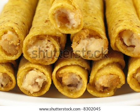 A plate of hot, crispy chicken taquitos. - stock photo