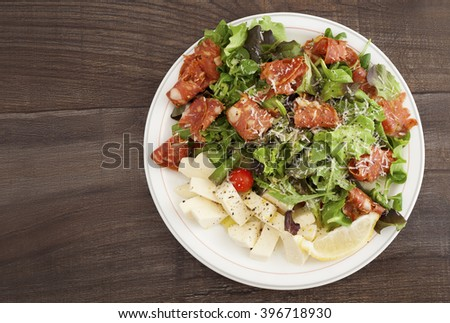 A plate of Italian salad with salami calabrese, cherry tomato, mozzarella, rucola, parmigiano and lemon.