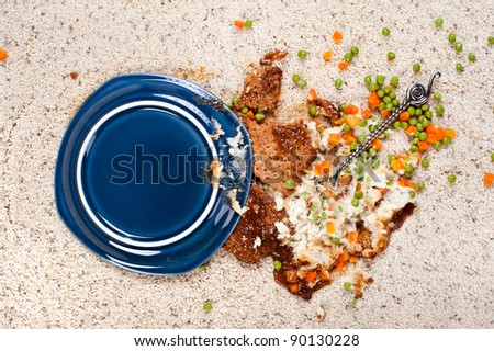 A plate of meatloaf with mashed potatoes and peas dropped on new carpet. - stock photo