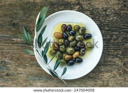 A plate of Mediterranean olives in olive oil with a branch of olive tree over a rough old wooden desk. Top view - stock photo