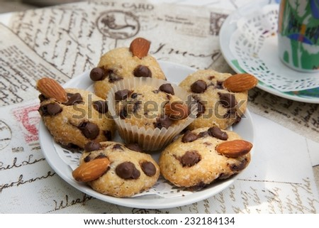 A plate of mini shortcakes with chocolate chips and almond nuts. A cup of espresso in the background