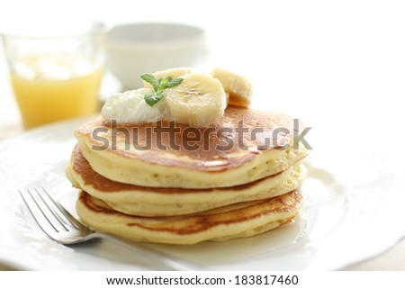 A plate of pancakes topped with banana and a glass of orange juice. - stock photo