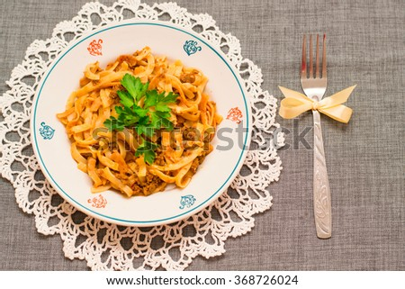 a plate of pasta and gravy on the table with festive napkin - stock photo