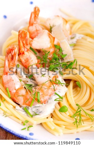 a plate of pasta topped with shrimp scampi and herbs