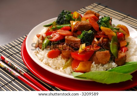 A plate of pork stir fry with vegetables - stock photo