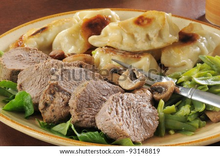 A plate of roast beef and potstickers with green beans