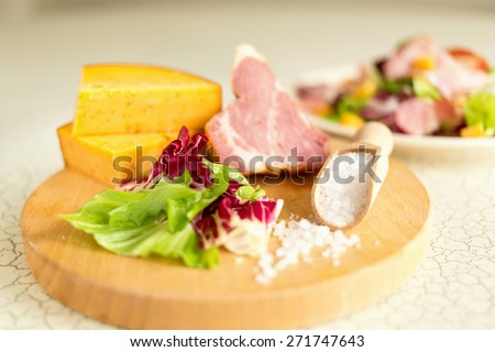 A plate of salad of green leaves, ham and cheese. Plate of salad with green leaves, ham and cheese. Fresh lettuce, cheese, ham and sea salt on a cutting board. Intercontinental breakfast at the hotel.