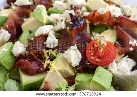 A plate of salad with bacon, avocado, sheep cheese, cherry tomato and lemon zest.