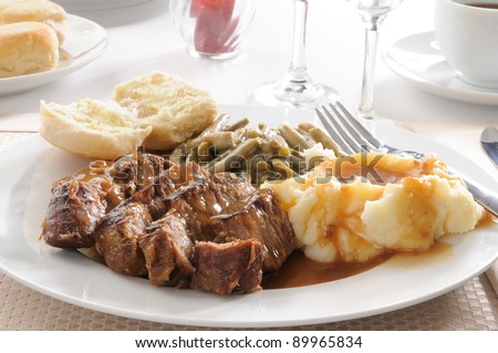 A plate of sliced beef pot roast with mashed potatoes and mushroom gravy - stock photo