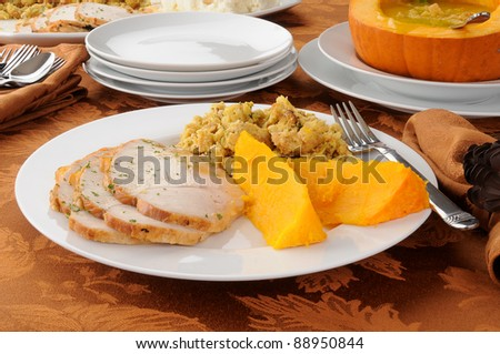 A plate of sliced turkey with butternut squash, dressing and pumpkin soup