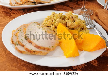 A plate of sliced turkey with dressing and butternut squash