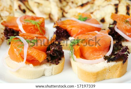 A plate of smoked salmon canapes on french bread, garnished with lettuce, dill and an onion ring