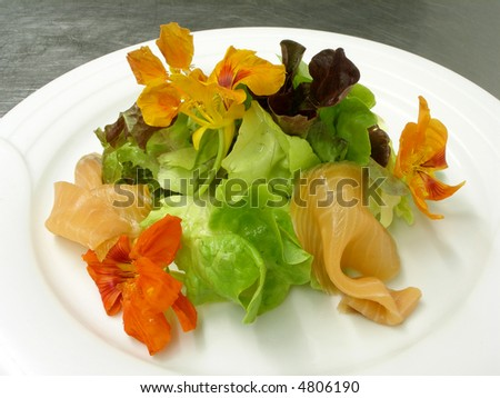 A plate of smoked salmon green leaves and nasturtium - stock photo