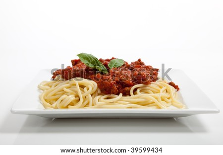A plate of spaghetti with meat sauce and basil on a white background - stock photo