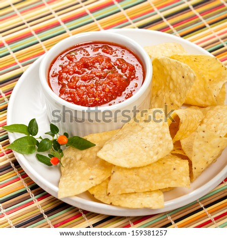 A plate of tortilla chips with salsa