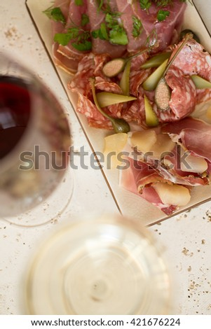 A plate of various deli meat or cold cuts and greens alongside two glasses of wine. - stock photo