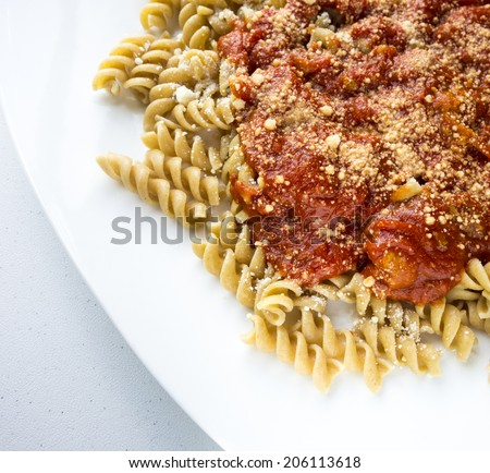 A plate of whole wheat spiral pasta with sauce and parmesan cheese. - stock photo