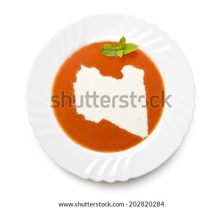 A plate tomato soup with cream in the shape of Libya.(series) - stock photo