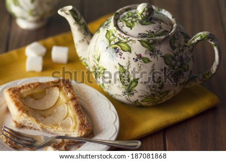 A plate with a apple pie and a fork. A teapot, a cup and three sugar cubes - stock photo
