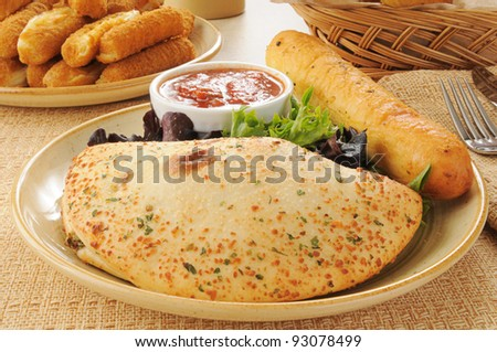A plate with a calzone and a brread stick - stock photo