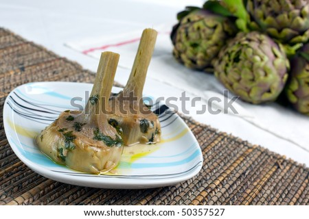 """a plate with a couple of artichokes hearts cooked """"alla romana"""" with parley mint and garlic. Fresh artichokes in the background. - stock photo"""