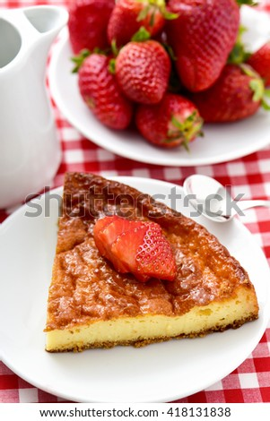 a plate with a piece of homemade cheesecake topped with sliced strawberry and a plate with ripe strawberries on a table set with a checkered tablecloth