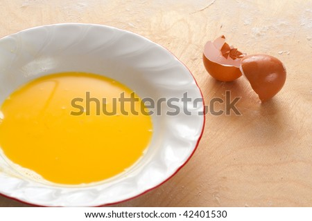 A plate with beaten egg yolks and a broken egg shell on a wooden and floured board