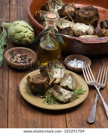 A plate with cooked artichokes,  served with olive oil,  pepper and salt on the  wooden table. - stock photo