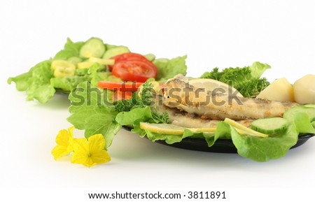 A plate with fried fish, on a background a plate with salad.