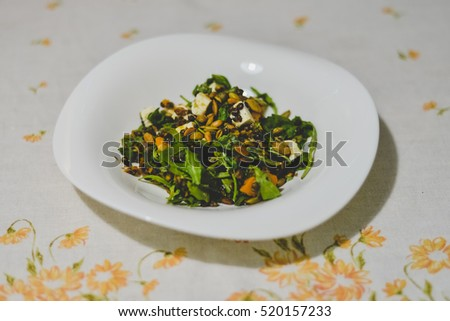 A plate with healthy pumpkin and lentil salad on a table with grey tablecloth.